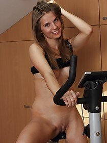 Dark-haired beauty teasing her pussy next to her gym equipment