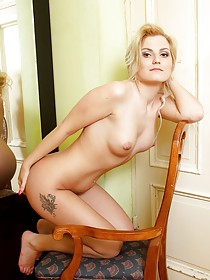 Blond-haired beauty checks out her reflection and loves what she sees