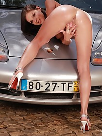 Green get-up brunette washing a fancy car and getting really wet